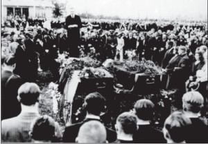 The caskets with the flyers' bodies arrive at Kaunas Airport. The representative of the U.S. government in Lithuania addresses the gathered crowd, which includes relatives of the flyers and high government officials.