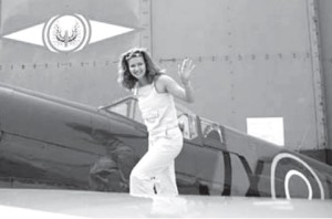 Journalist Gražina Sviderskytė next to a WW II vintage Hurricane fighter aircraft.