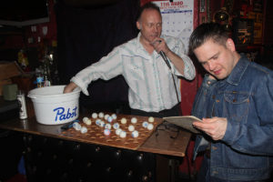 "Steve Badauskas announces the winning numbers for ""STINGO"" (BINGO) while Keith Judge double checks his card."
