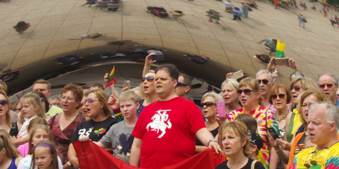 Lithuania's Consul General in Chicago Marijus Gudynas leads his compatriots in the singing of the Lithuanian national anthem at Chicago's popular tourist attraction – the Bean.