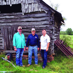 By the Lithuanian log shed: (from left) owner Delbert Derryberry, new president of the Oklahoma Lithuanian Club Jim Grego-Grigalevičius, and author Vilius Žalpys.