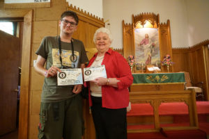 "Augustinas Žemaitis presenting a certificate to church secretary Vicki Nicely stating that Jerusalem Lutheran Church is an ""authentic Lithuanian heritage site."""