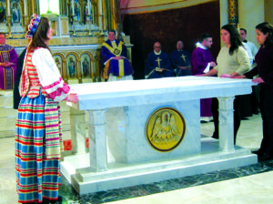 Monika Kungienė (left) with other parishioners cover the altar in a solemn ceremony.
