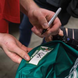 Domantas pasirašo savo marškinėlius.