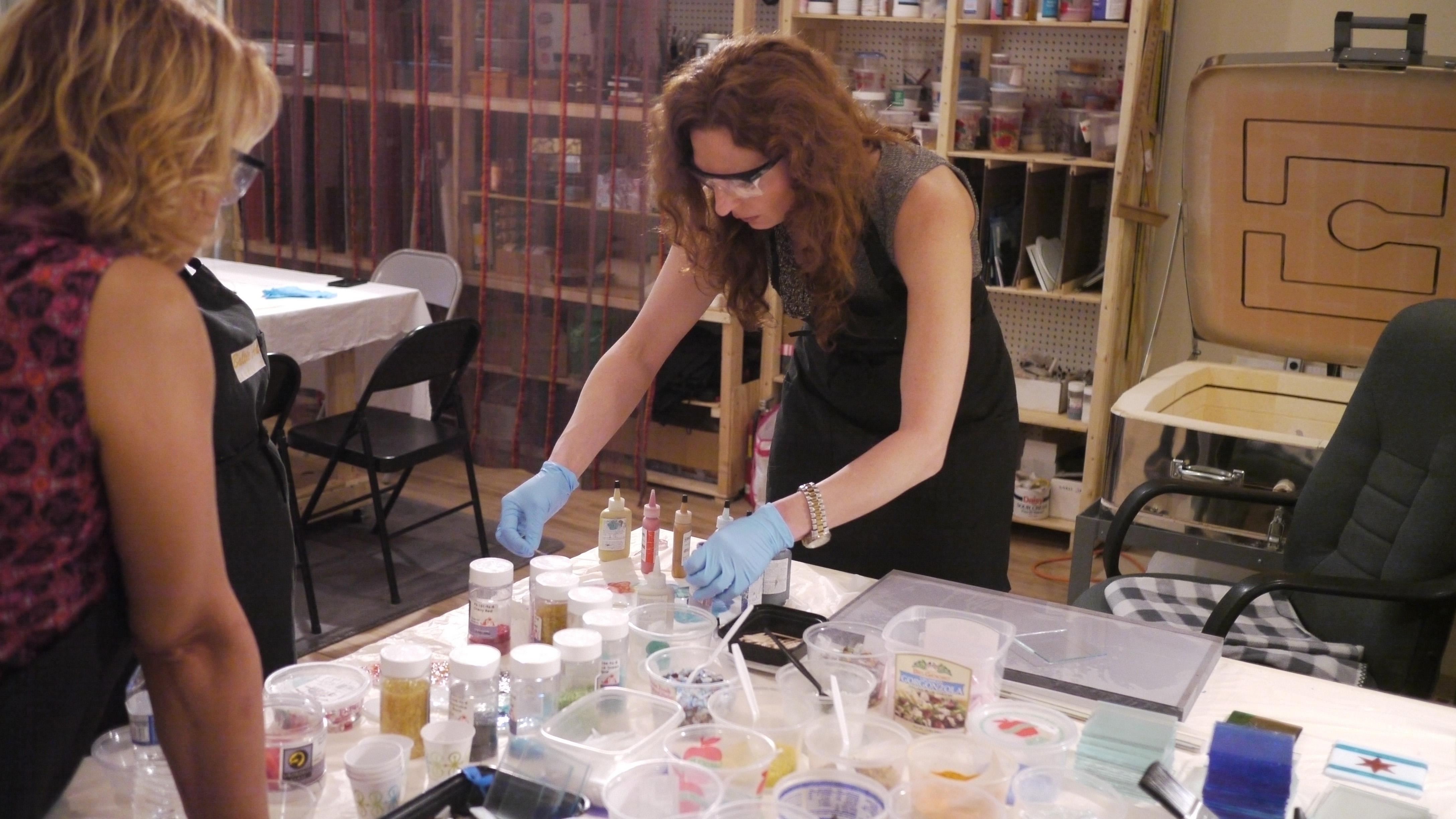 Evelina susirinkusiems rodo kaip pasiruošti dažus stiklo dirbų dekoravimui.