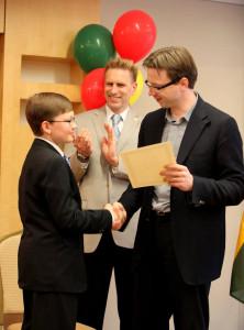 Lietuvos ambasadorius JAV Rolandas Kriščiūnas įteikia Augustui mokyklos baigimo pažymėjimą, kuriuo džiaugiasi ir istorijos mokytojas Audrius Kirvelaitis.