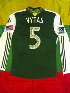 """Ant V. Andriuškevičiaus marškinėlių nugaros puikuojasi užrašas """"Vytas""""."""