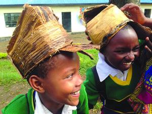 Vaikai pasipuošę mamos Karo darytomis kepurėmis.