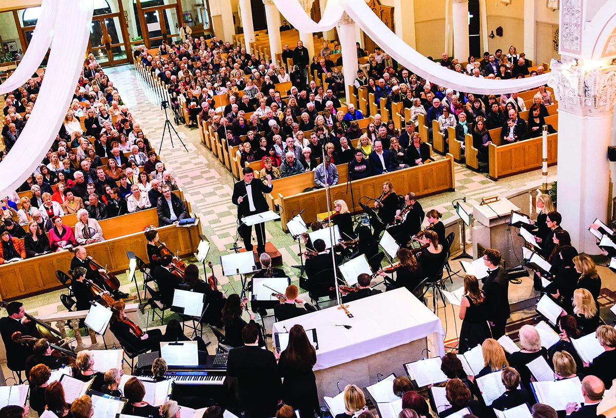 """Dirigento Dariaus Polikaičio vedamas """"Dainavos"""" ansamblis su solistais ir orkestru atlieka Mozarto """"Missa brevis B-dur""""."""