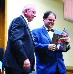 """J. Polikaitis įteikia M. Gudynui 63 organizacijų nuotraukų ir sveikinimų knygą """"Tobula"""" bei skaitmeninių """"Draugų"""" dvitomį, kuriame atsispindi 5-erių metų konsulato veikla."""