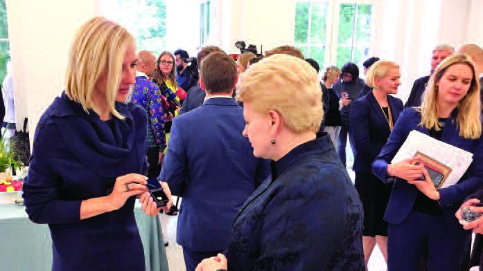 """Projekto """"To Be LT"""" vadovė A. Vertelkaitė įteikė Prezidentei D. Grybauskaitei iniciatyvos simbolio tautiškos lelijos ženkliuką."""