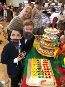 Mokyklos direktorė Marytė Newsom su ketvirtokais Deiviu Danovitch (J. Basanavičius) ir Povilu Gaidžiu (A. Smetona) pasiruošę pjauti šventinį tortą.