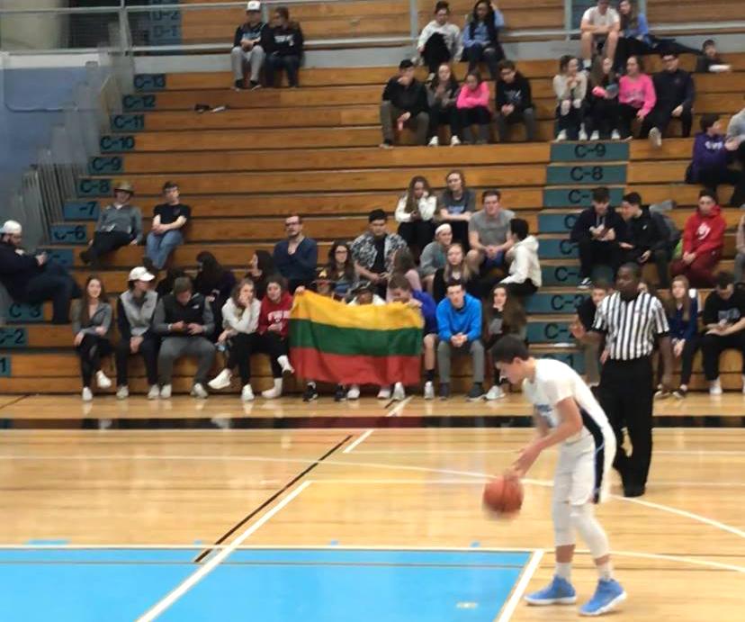 """Matas rungtynėse prieš """"Larkin"""" krepšinio komandą meta baudas, o sirgaliai mojuoja lietuviška vėliava."""