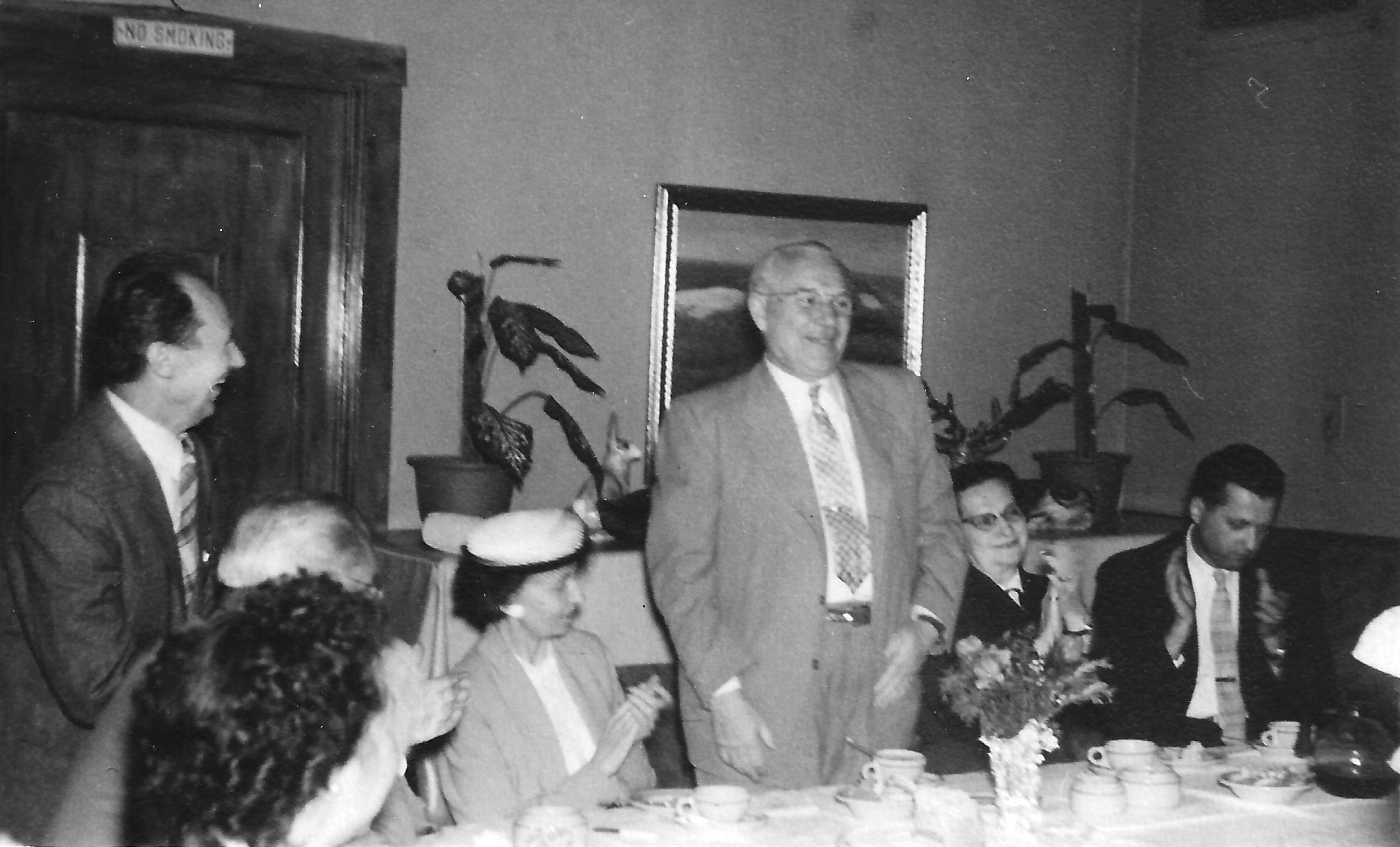 Frank Rakas (v.) praneša apie savo dovaną. Kairėje stovi V. Pavilčius, šalia F. Rako sėdi Milda Budrienė, kitoje pusėje Biežienė ir Stasys Budrys.