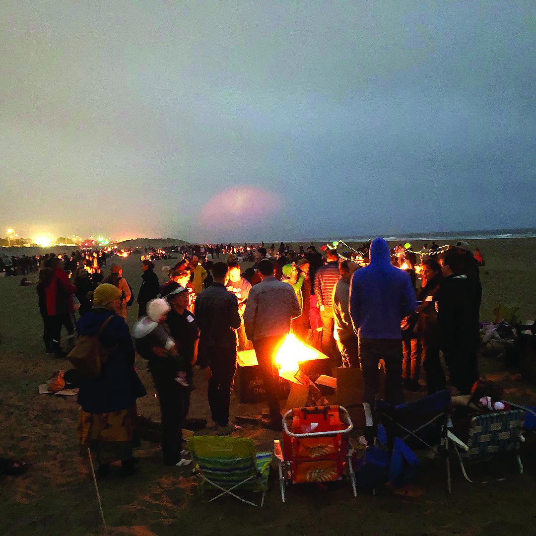 """Ramiojo vandenyno pakrantėje Ocean Beach paplūdymyje prie laužo susirinkę lietuviai, latviai ir estai uždegė laužą ir taip prisijungė prie Baltijos šalių renginio """"Senovinė ugnies naktis – šimtmečio laužai""""."""