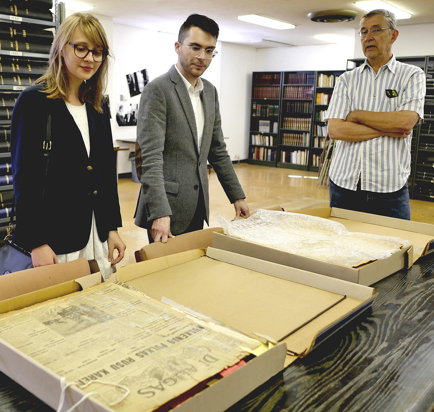 """""""Draugo"""" redakcijoje Jonas Daugirdas (d.) kartu su William Shalaack ir Anna Oates, svečiais iš University of Illinois at Urbana-Champaign apžiūri senuosius """"Draugo"""" numerius."""